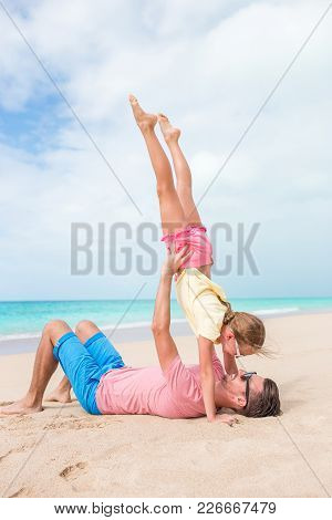 Happy Father And His Adorable Little Daughter At Tropical Beach Having Fun Together