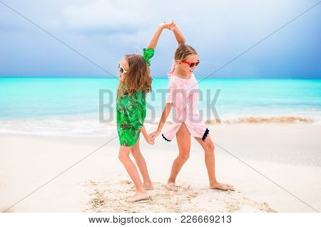 Little Girls Having Fun At Tropical Beach Playing Together At Shallow Water.