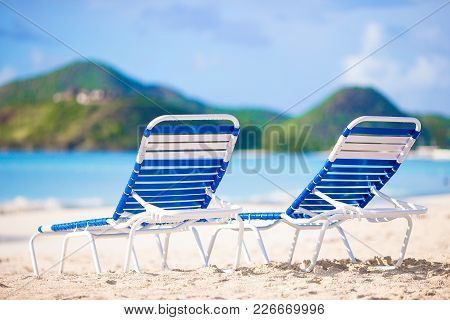 White Lounge Chairs On Beautiful Tropical Beach At Maldives
