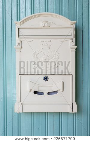 White Vintage Mailbox Hanging On A Wooden Wall In Turquoise