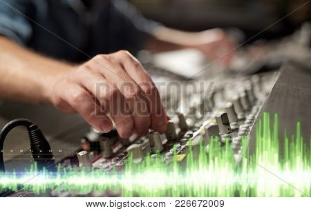 music, technology and equipment concept - male hands using mixing console in sound recording studio