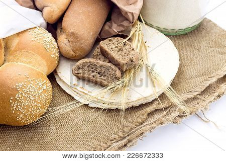 A Variety Of Bakery Products And Spikelets Of Wheat  On A White Background Close-up