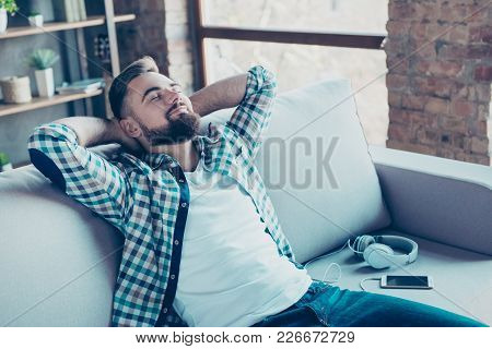 Single, Happy Young Man In Checkered Shirt Is Relaxing On The Sofa At Home With Close Eyes, Hands Be