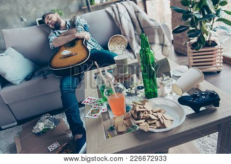 After Party Morning, Bachelorette Party. Drunk Hipster Embracing An Acoustic Guitar Is Sleeping On A