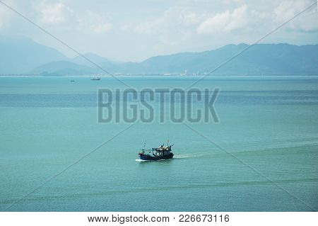 Vietnamese Fishing Boat At Sea, With A Backdrop Of Hills.