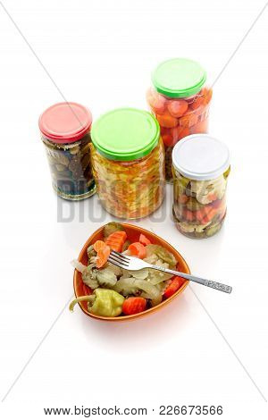 Different Marinated Vegetables In A Bowl And Jars On A White Background Close-up