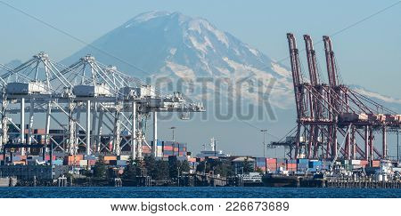 Container Cranes Loom Over Duwamish Waterway With Mount Rainier In The Background.