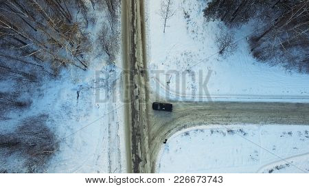 Top View Of The Car Riding In The Woods. Footage. The Car Goes On A Winter Road In The Woods.