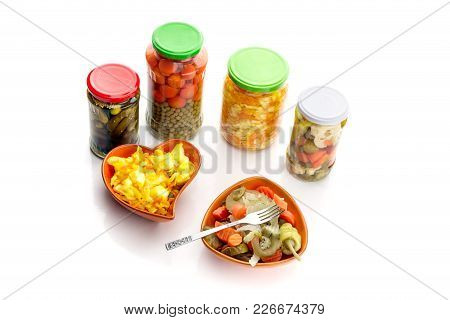 Different Marinated Vegetables In Cans And Bowls On White Background Close-up.