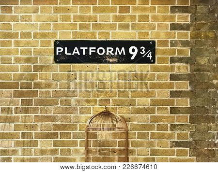 Sign With 9 3/4 On It With A Cage Below Against A Brick Wall At Kings Cross Station.
