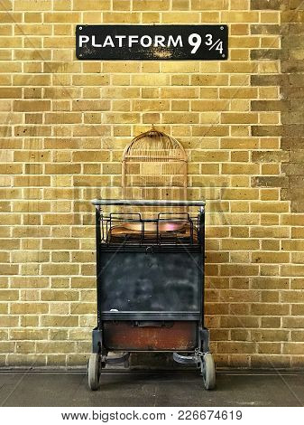 Sign With Platform 9 3/4 On It, Above A Trolley With Suitcases And An Empty Bird Cage Against A Bric