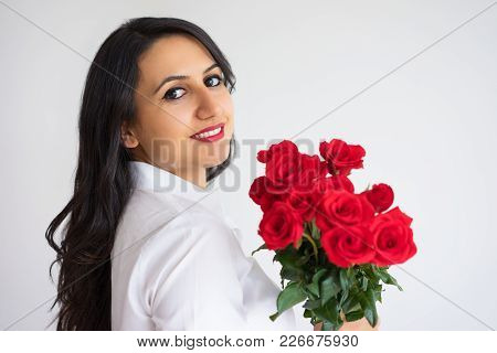 Content Beautiful Young Businesswoman With Bouquet Of Roses Looking At Camera. Cheerful Attractive W