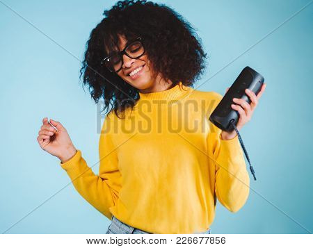 Young Beautiful African Woman Enjoying And Dancing At Blue Background. Modern Trendy Girl With Afro