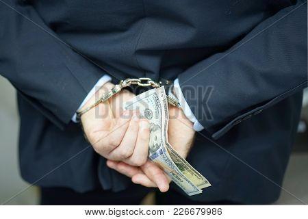 Close-up. Businessman In Office In Handcuffs Holding A Bribe. Prisoner Or Arrested Terroristin Handc