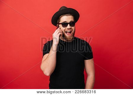 Portrait of irresistible fancy man 30s in sunglasses wearing black t-shirt and hat smiling and talking on mobile isolated over red background