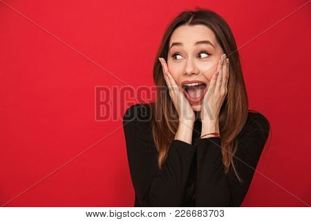 Photo of screaming excited young woman standing isolated over red background. Looking aside.