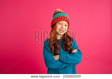 Cheerful ginger girl in blue warm sweater looking camera and smiling isolated over pink