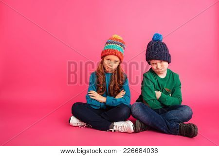 Sad ginger brother and his little beautiful sister sitting on floor with folded hands and looking camera isolated