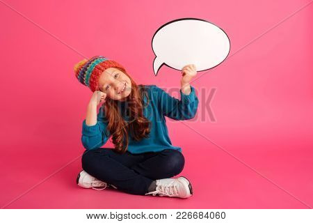 Cheerful ginger girl in hat holding bubble speech and looking camera while sitting on floor