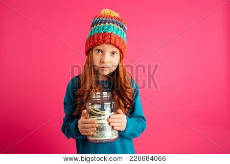 Thoughtful upset girl in knitted clothes looking camera and holding money box
