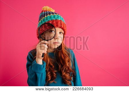 Funny serious ginger girl looking through magnifying glass at camera isolated over pink