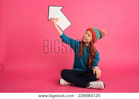 Cheerful girl in coloured hat looking awayand holding blank arrow up isolated over pink