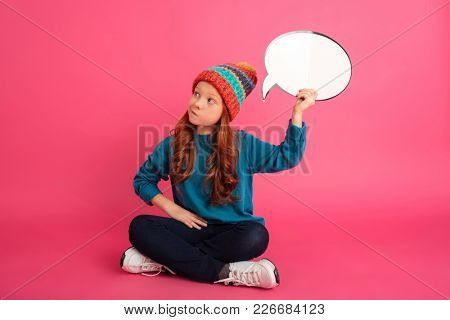 Thoughtful ginger girl in knitted hat looking up and holding bubble speech isolated