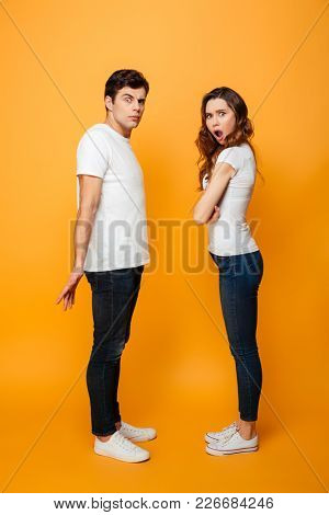 Full length image of Displeased Young couple looking at the camera over yellow background