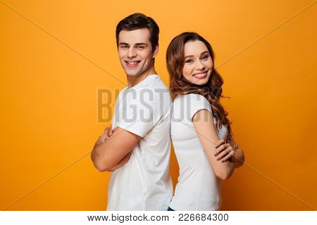 Portrait of a happy young couple standing with arms folded standing back to back isolated over yellow background