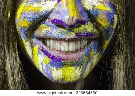 Portrait Of Beautiful Young Woman With Colorful Oil Painting On The Face. Smile Close Up.  Dental Se