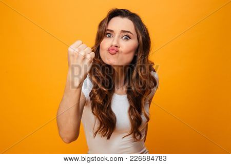 Displeased brunette woman in t-shirt showing her fist and looking at the camera over yellow background