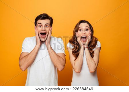 Portrait of an excited young couple screaming isolated over yellow background