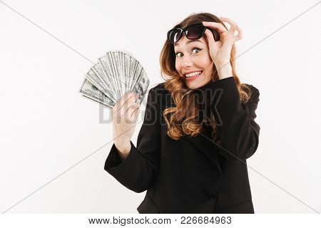 Portrait of an excited young businesswoman dressed in suit showing bunch of money banknotes isolated over white background