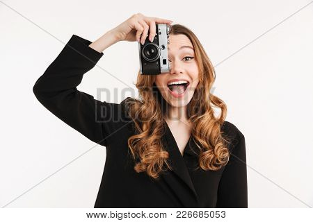 Portrait of an excited young woman dressed in suit taking a photo with camera isolated over white background