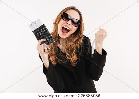 Portrait of an excited young woman dressed in suit showing passport with flying tickets isolated over white background