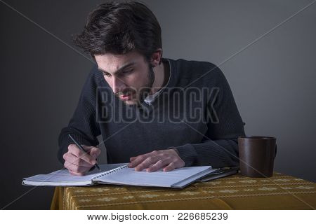 Young Student Solving Math Problems Or Writting An Essay In His Notebook And Drinking Coffee