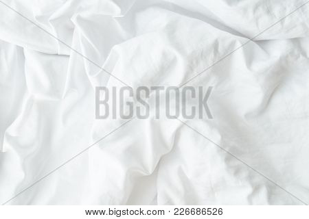 White Wrinkled Fabic Texture, Close Up Unmade Bed Sheet In The Bedroom After Night Sleep Soft Focus.
