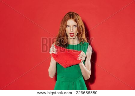 Displeased ginger woman in green dress holding joy heart and looking at the camera over red background
