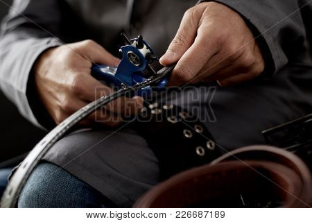 closeup of a young caucasian worker man, wearing a gray working coat, making a hole in a belt with a leather punch