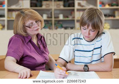 Teacher Teaches A Pupil At A Table In The Classroom