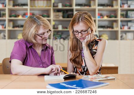 Teacher Teaches A Student At A Table In The Classroom