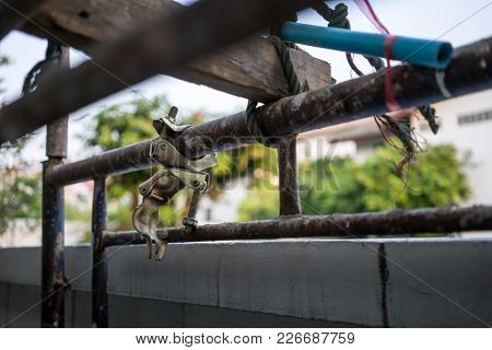 Rusty Metal Structure In Construction Site With Metal Tube Pole Or Pipe Clamp. Selective Focus