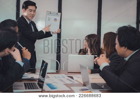 Businessman Present Financial Plan Report To Co Worker Team. Man Leader Discuss Sales Data With Inve