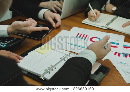 Young Business People Having A Meeting. Businessman & Businesswoman Working With Financial Chart Rep