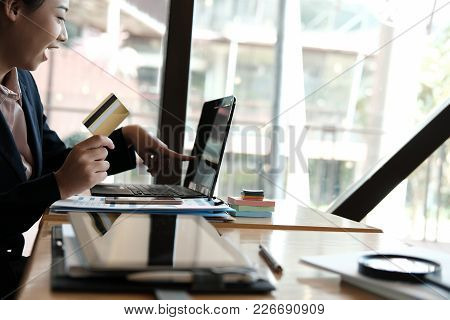 Woman Holding A Credit Card And Using Computer For Online Shopping At Cafe. Businesswoman Purchase G
