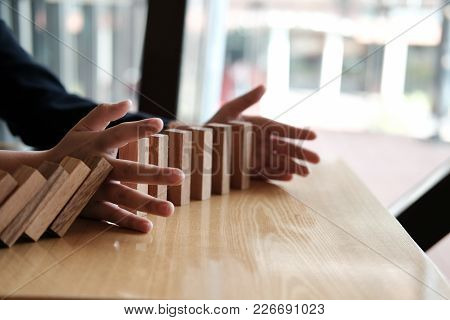 Hand Stopping Effect Of Domino Continuous Toppled. Busineeman Protecting Falling Wood Block. Solutio