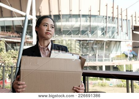Frustrated Woman Holding Cardboard Box Containing Personal Belongings After Being Fired & Layoff By