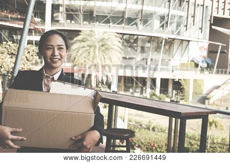 Happy Woman Resigning Her Job & Holding Cardboard Box Containing Personal Belongings. Resignation Co