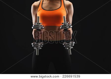 Unrecognizable Athletic Young Woman With Dumbbells On A Black Background. Studio Shot, Low Key, Copy