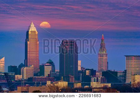 The Full Moon Of December, A Supermoon, Rises Through Clouds Above Downtown Cleveland, Ohio